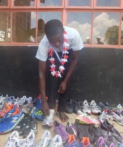 Young Kenyan Runner Picking Shoes