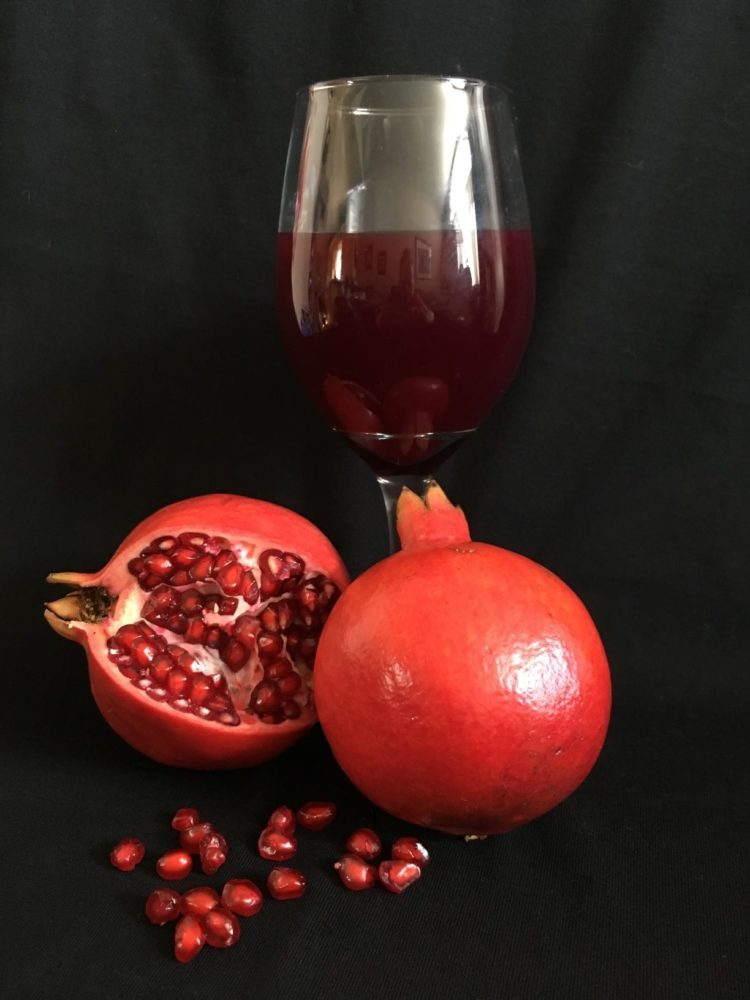Two pomegranates on a black background.  Wine glass with pomegranate juice in back ground.  Pomegranate seeds in foreground.